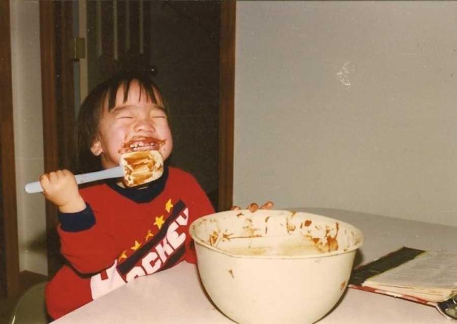 young boy licking spatula