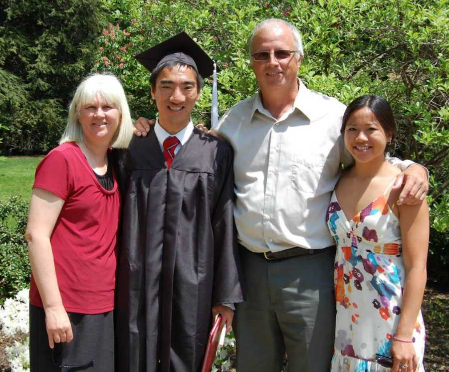 boy in graduation cap and gown with family