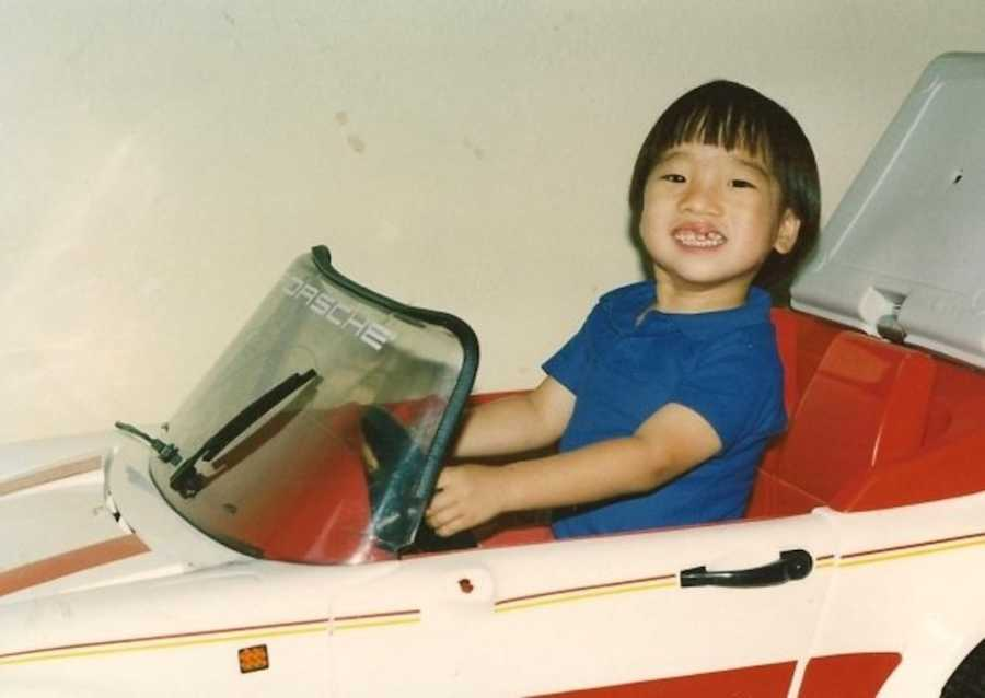 young boy in toy car