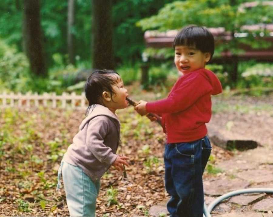 two siblings playing outside