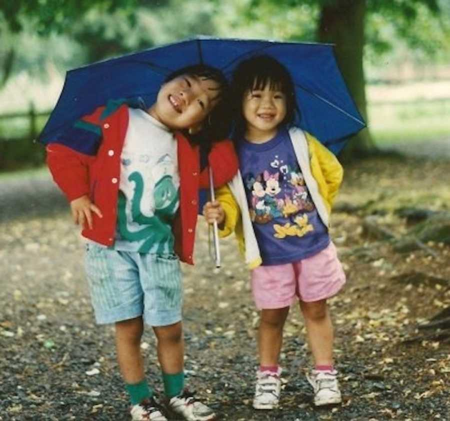 two siblings under an umbrella