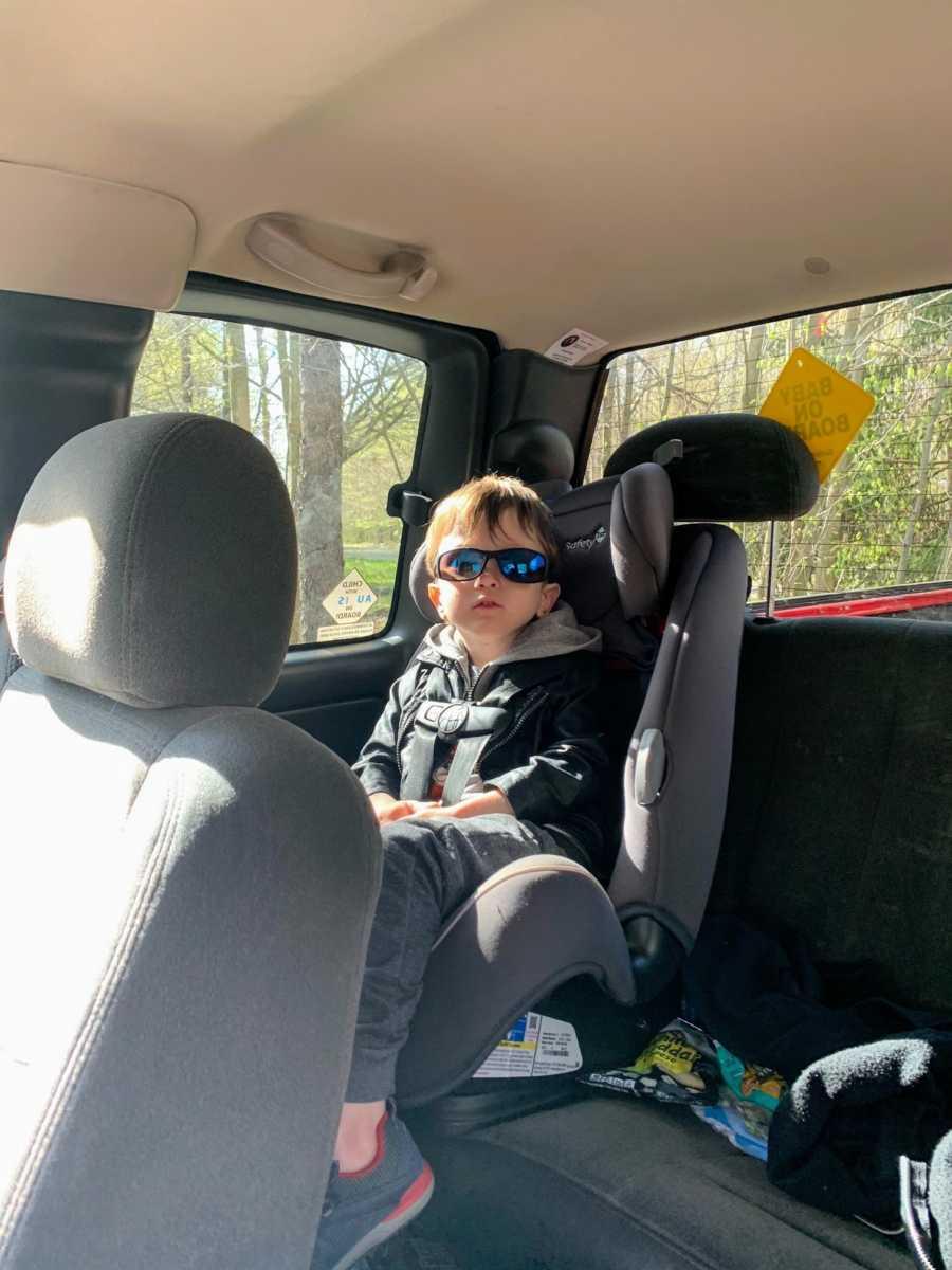Autistic boy in car seat wearing sunglasses