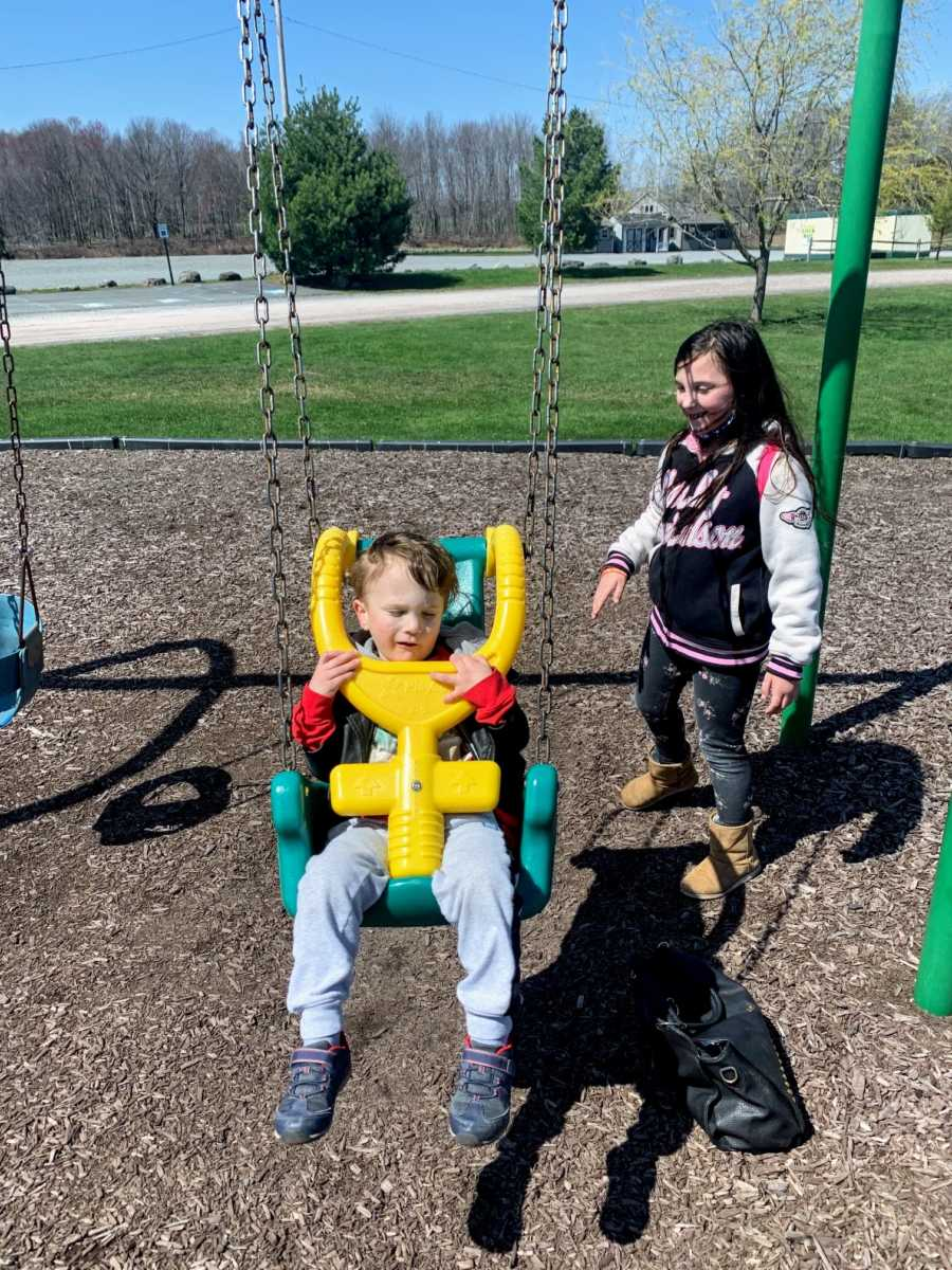 Sister pushes autistic brother on swing