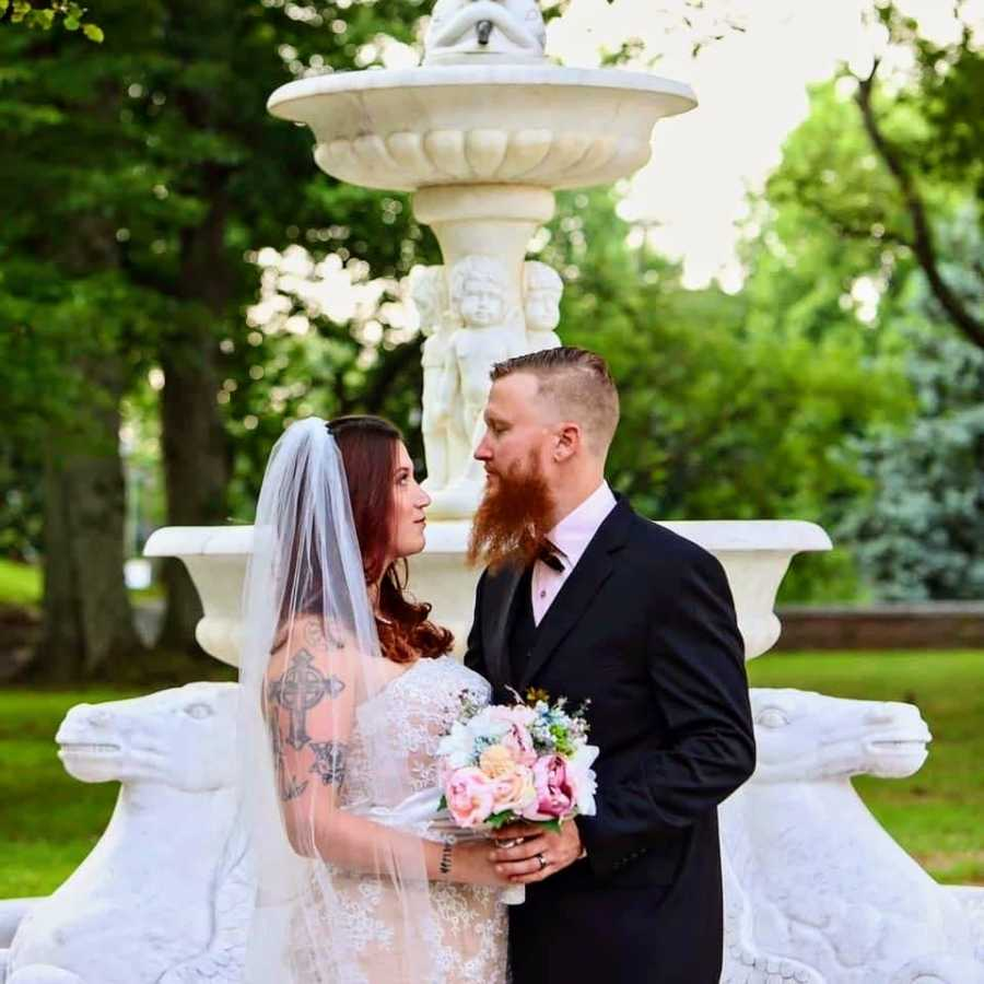 Bride and groom holding flowers near fountain