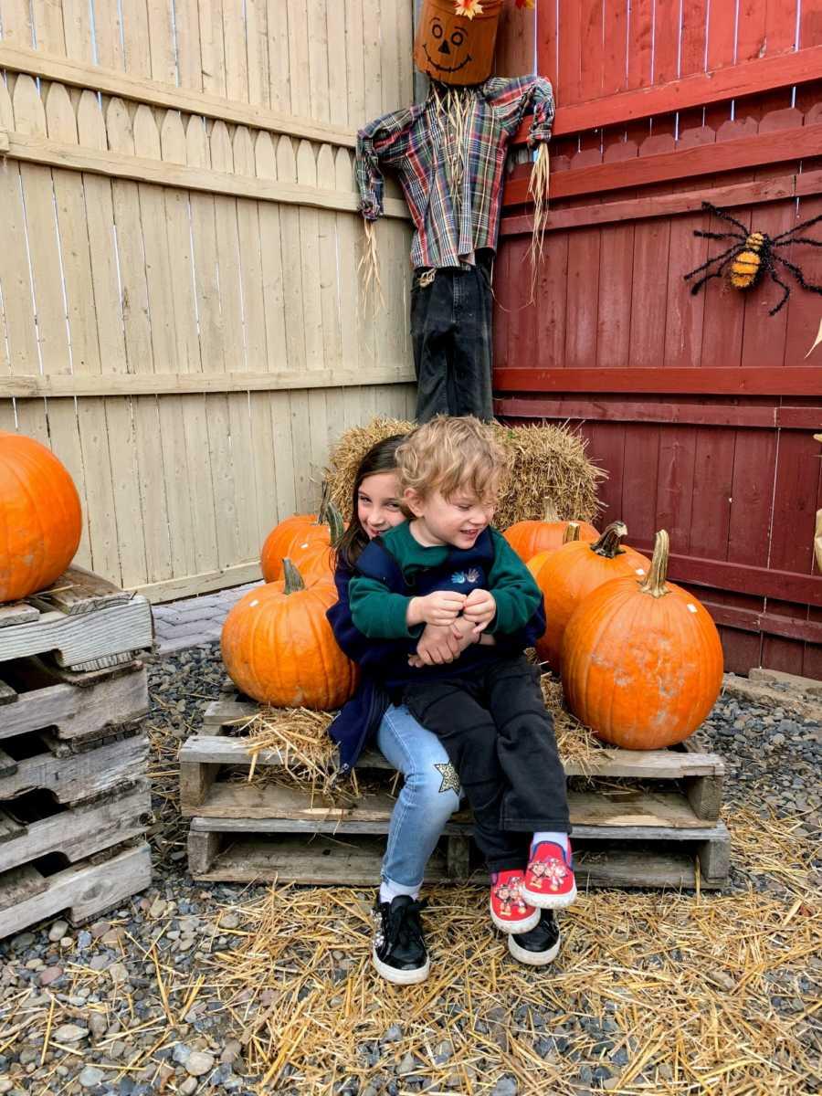 Girl hugs autistic brother on lap near pumpkins