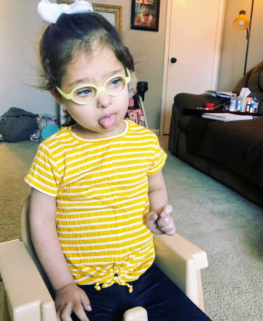 A girl with Down Syndrome wearing glasses sticks her tongue out
