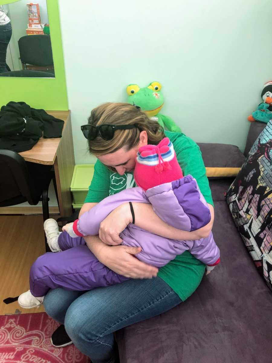 An adoptive mom holds her special needs daughter for the first time