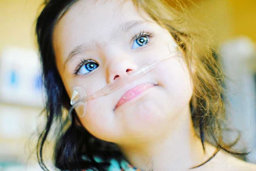 A girl with special needs wearing an oxygen tube