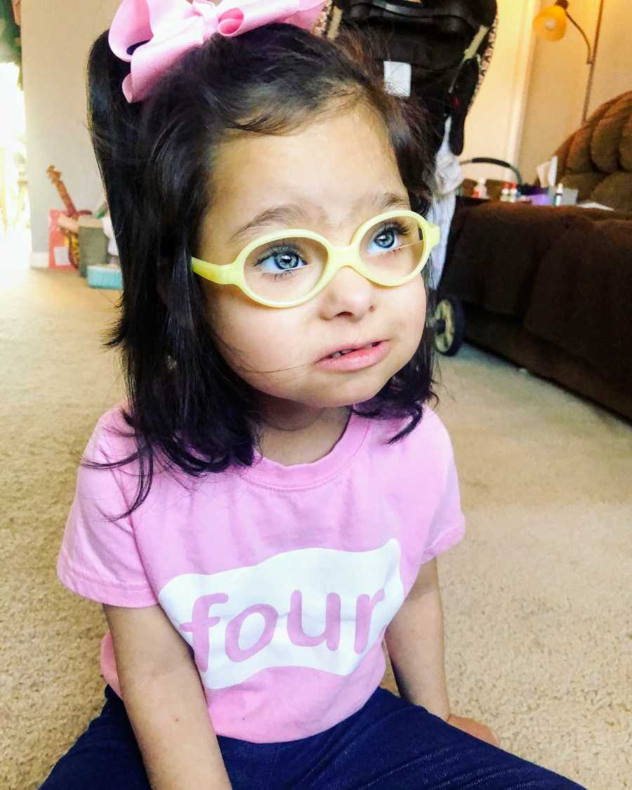 A girl with Down Syndrome wearing yellow glasses