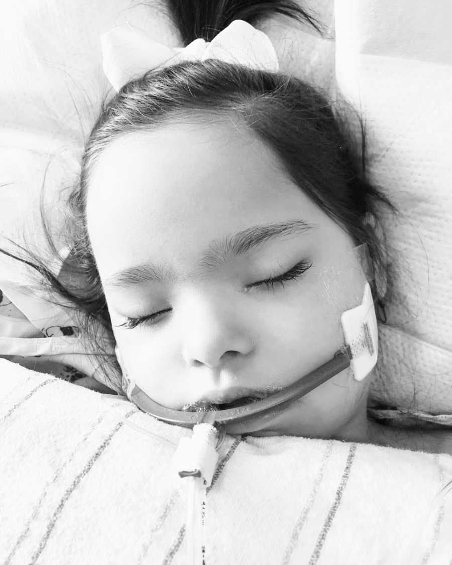 A girl with Down Syndrome lays with a tube in her mouth