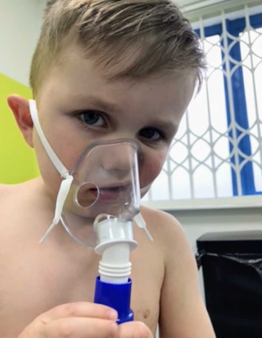 Young blonde boy wearing oxygen mask at hospital