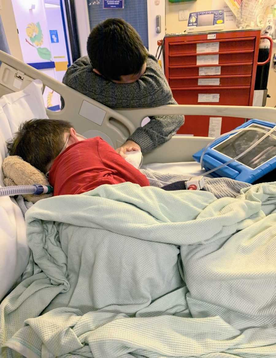 Young boy in hospital bed with tablet and father holding his hand