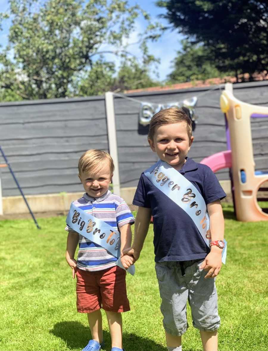 """Two brothers holding hands wearing """"big brother"""" sashes"""