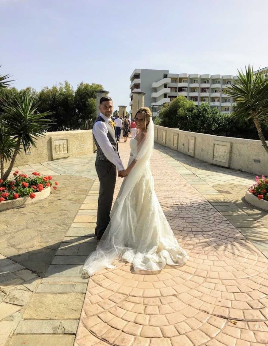 Newlywed couple standing while holding hands and looking at camera