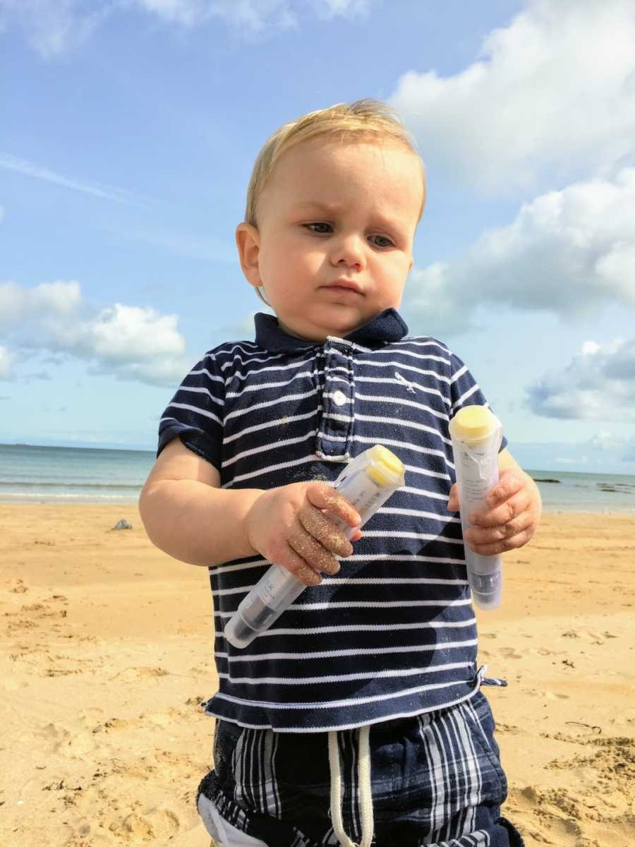 Blonde toddler at beach holding two EpiPens