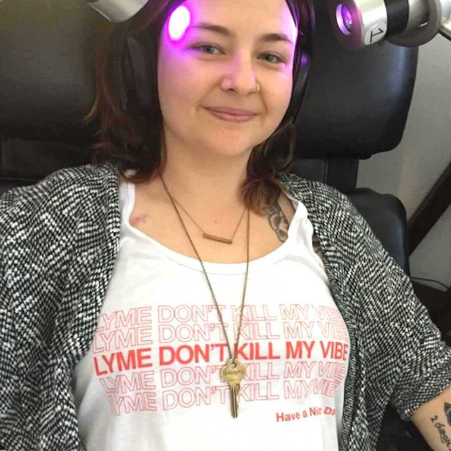 Woman sitting in a chair with two purple lights shining on her head