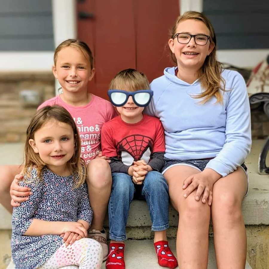 Siblings with foster brother smiling on porch together