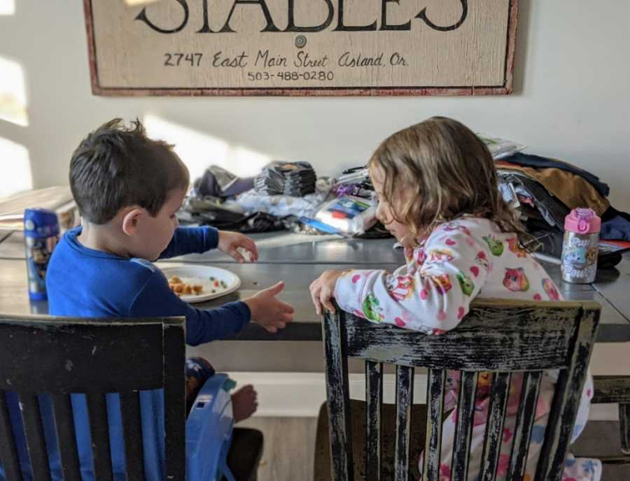 Foster son and sibling eating breakfast together at table talking to each other