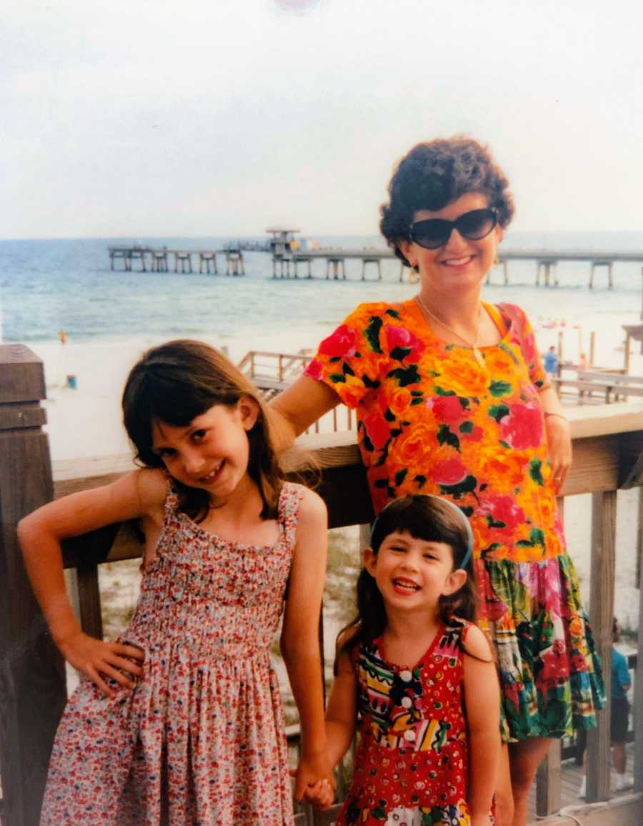 A mother stands in front of a beach pier with her two young daughters