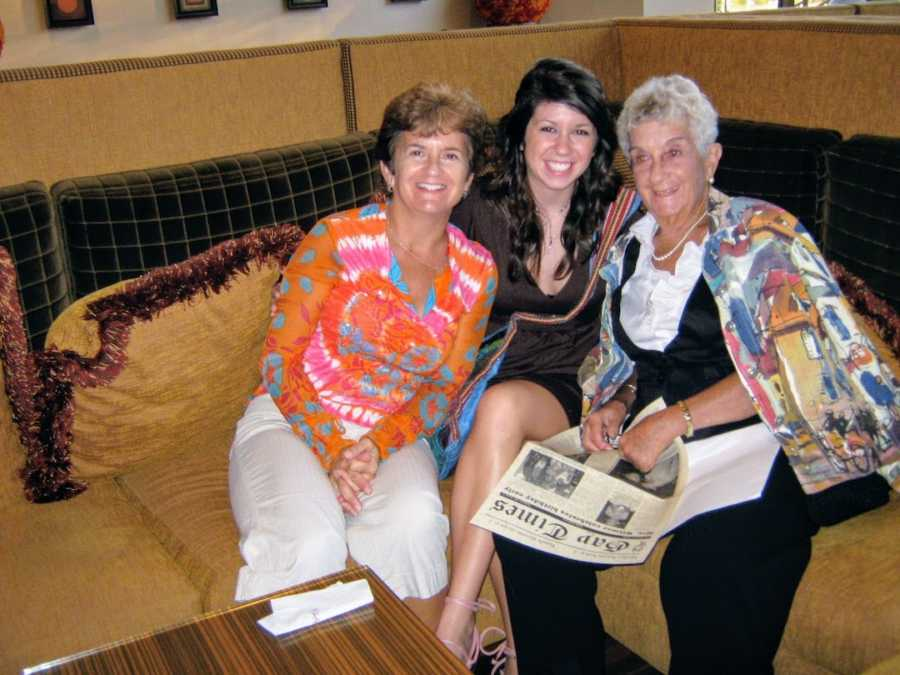 A grandmother, mother, and daughter sit on a couch smiling