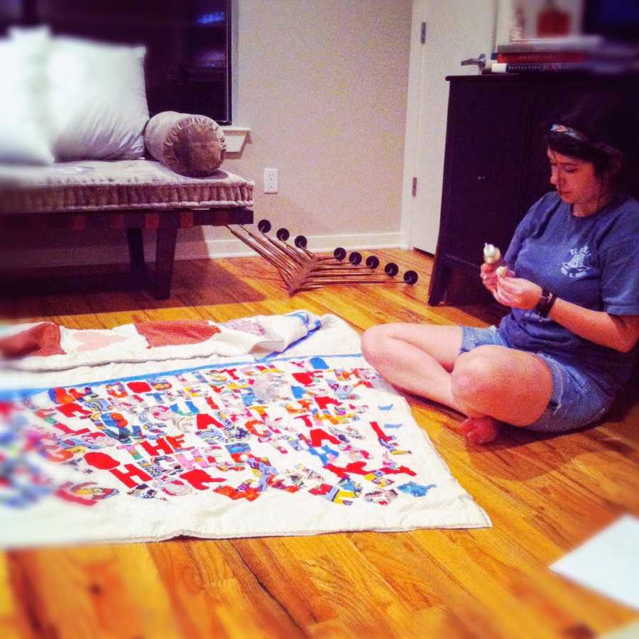 A woman crafts a quilt while sitting on the floor