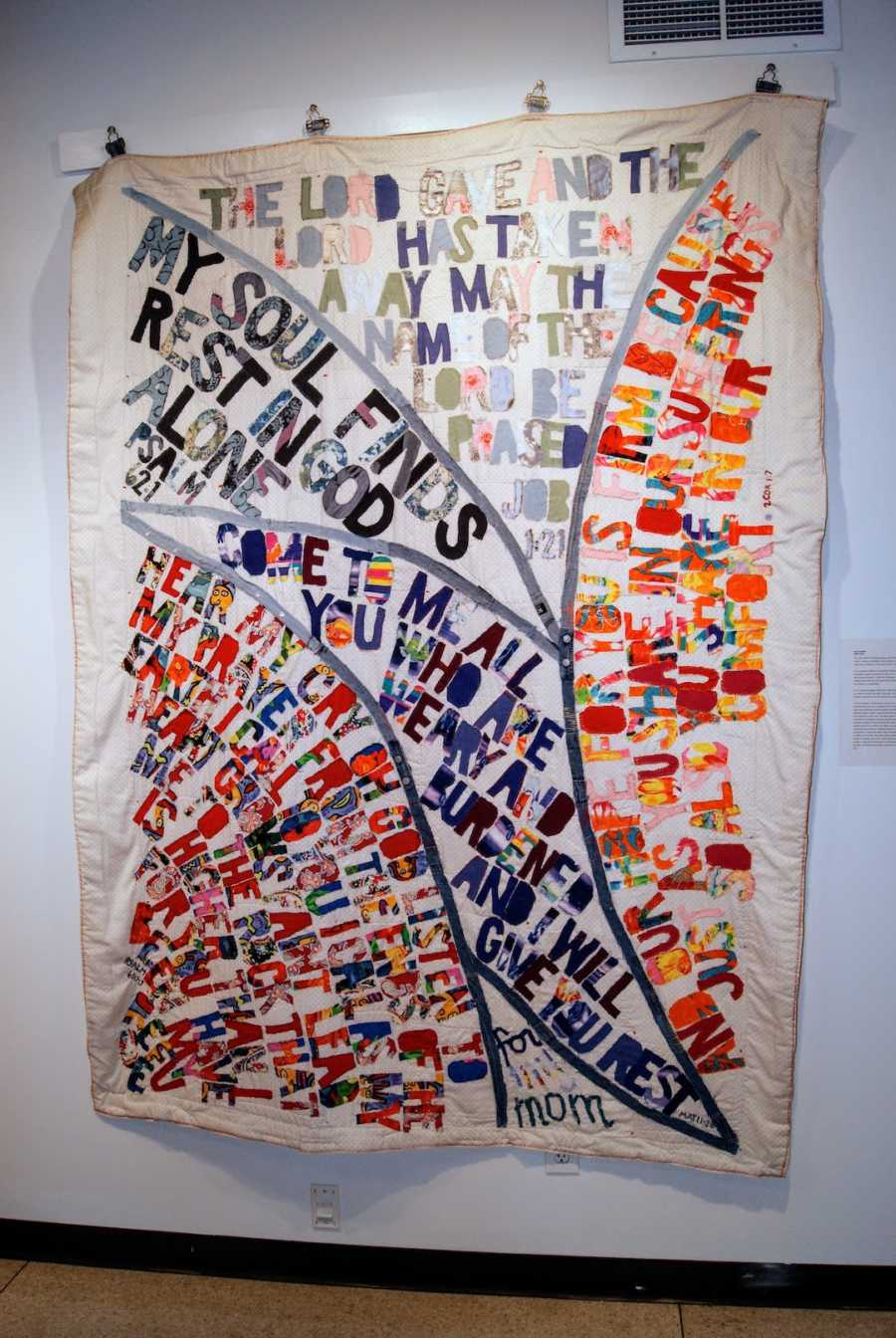 A quilt pinned to a white wall with Bible verses