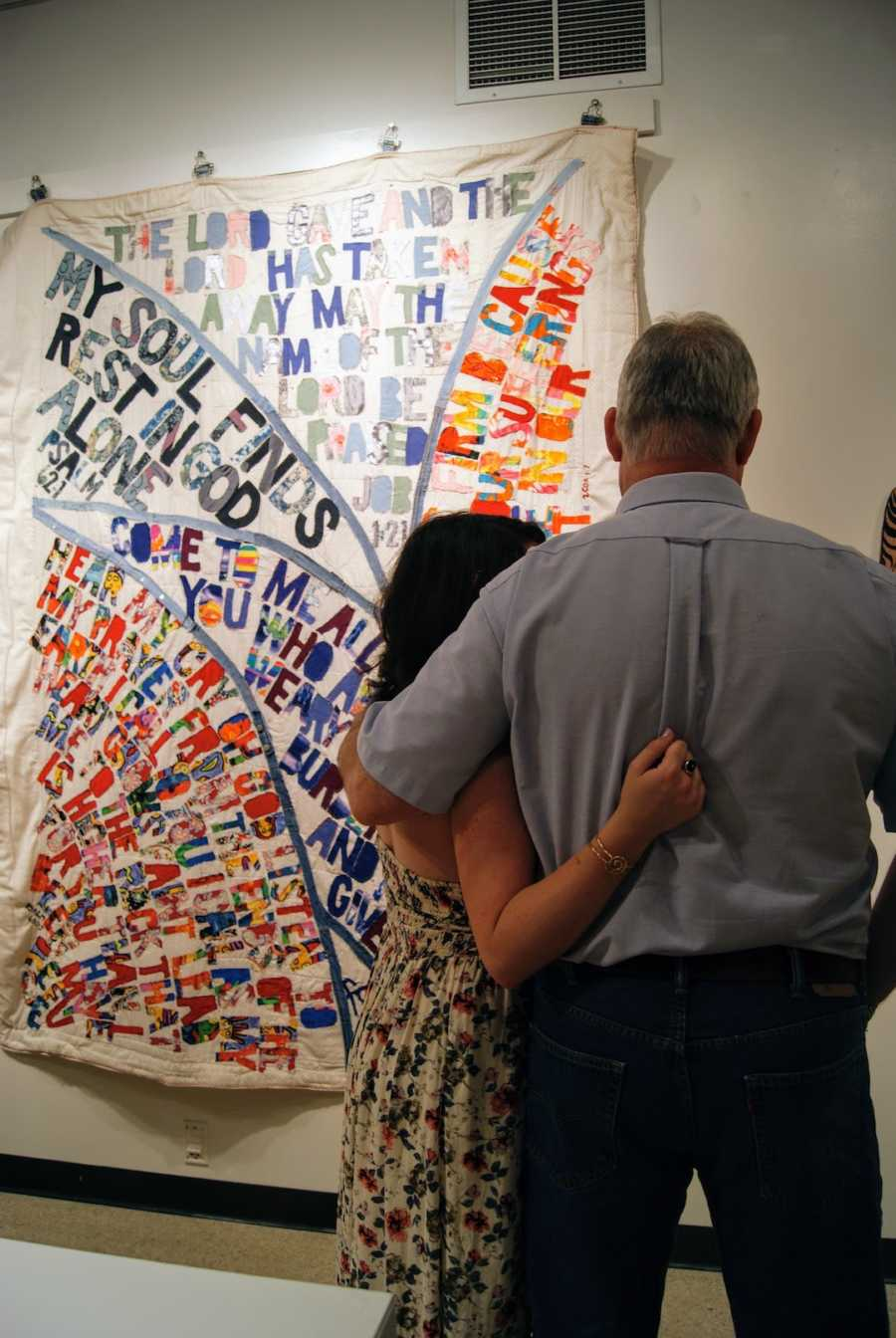 A father and daughter hug in front of a quilt pinned to a wall