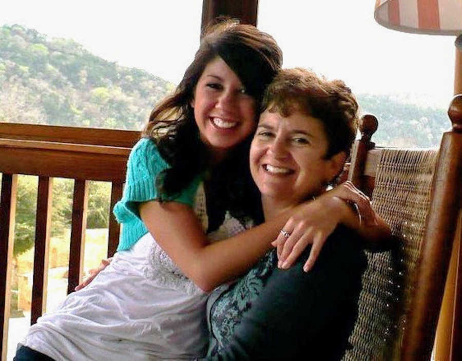 A mother and daughter sit in a rocking chair hugging