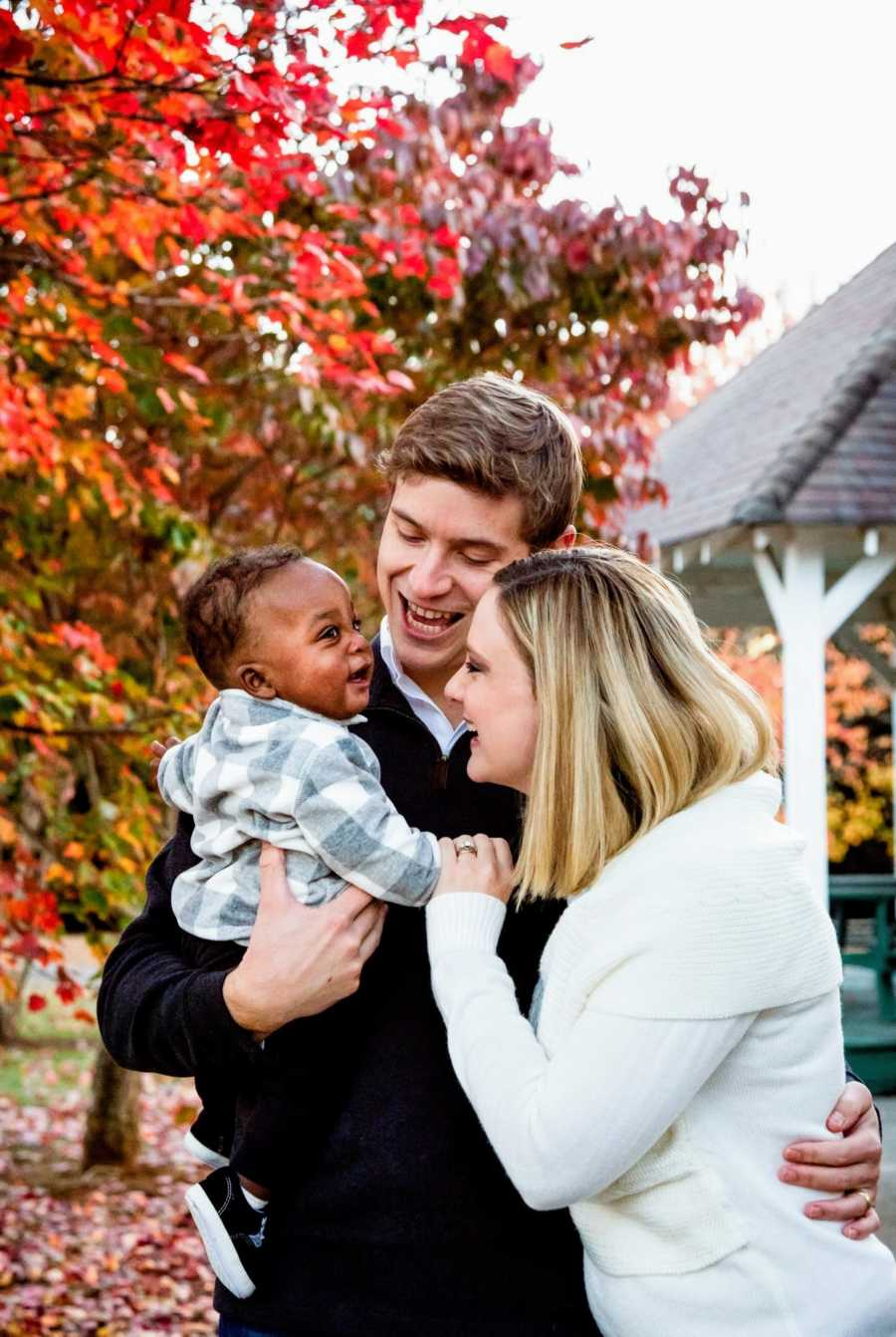 Adoptive parents and their son together in the fall