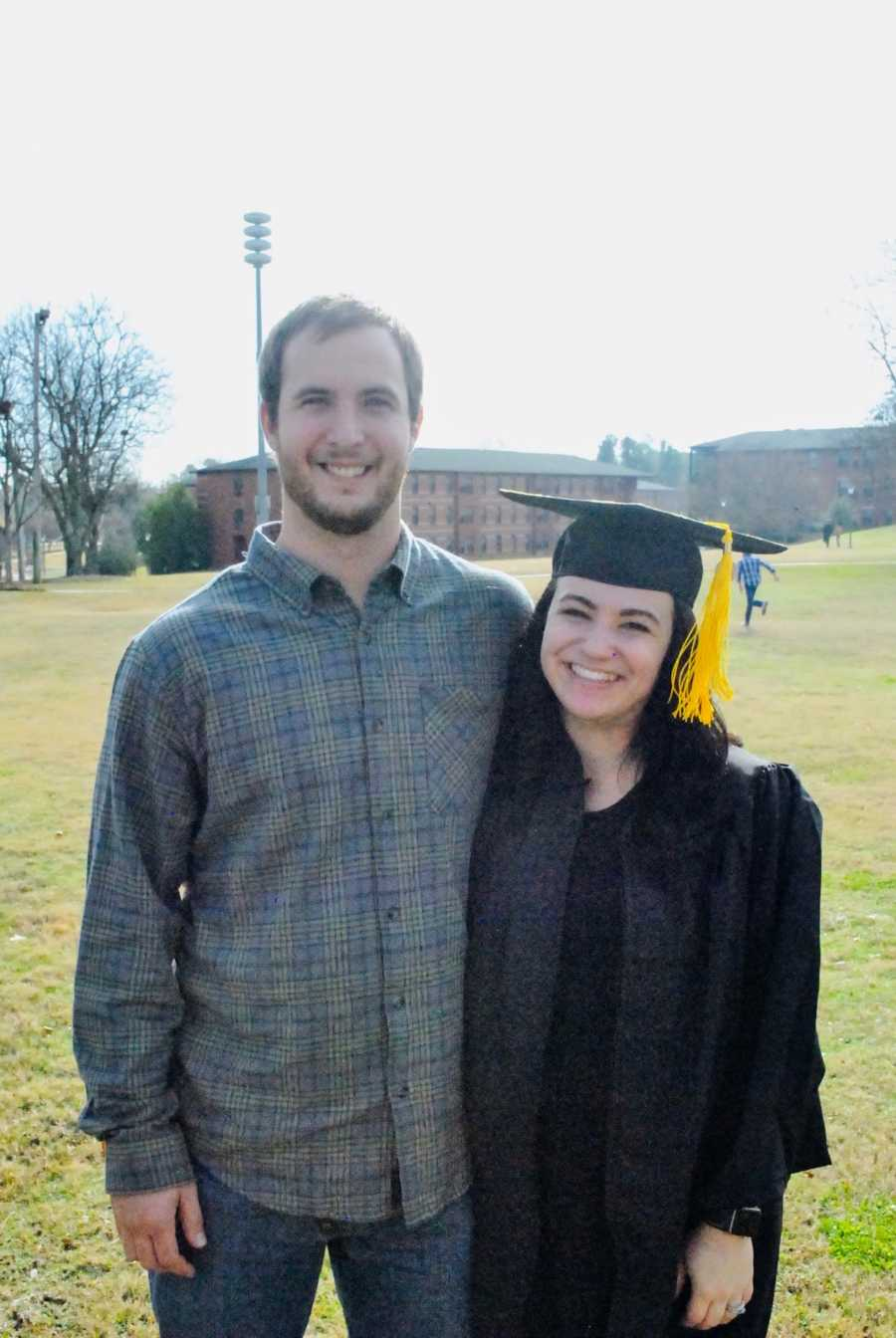 A young pregnant couple smiling after graduation