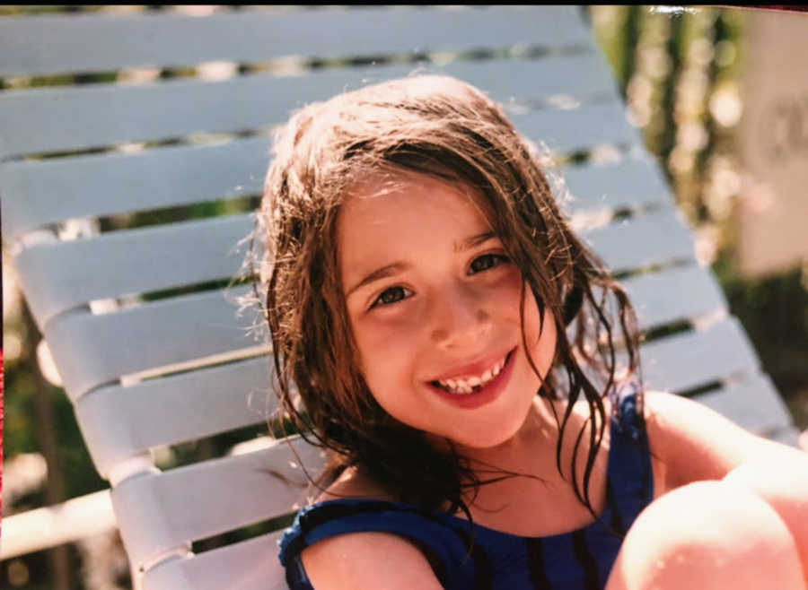Child sitting by a pool smiling