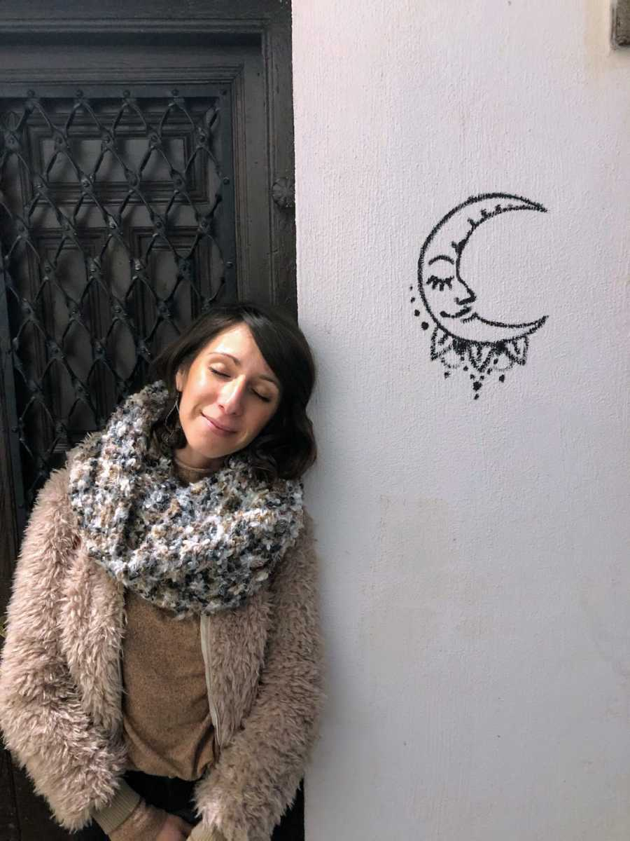 Woman smiling leaning on white wall with moon drawing