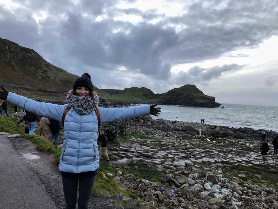 Woman smiling with arms outstretched in front of ocean