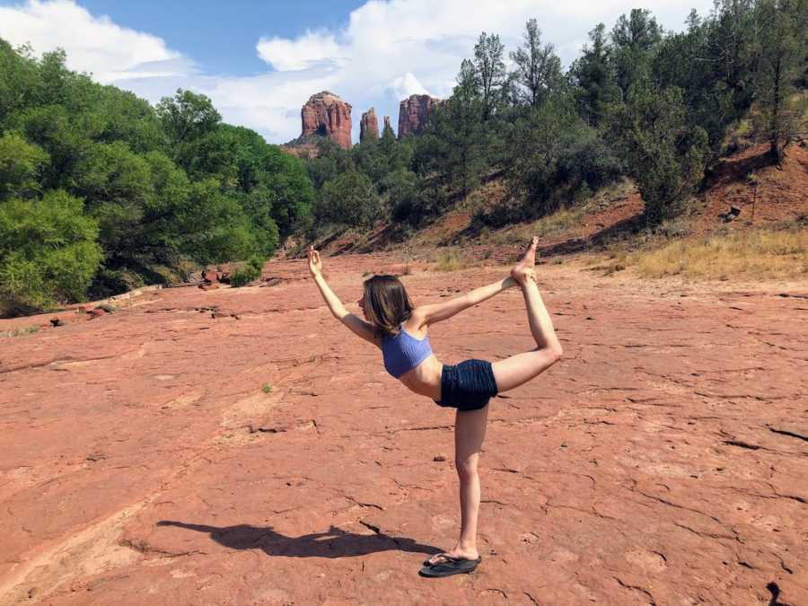 Woman doing warrior yoga pose in desert