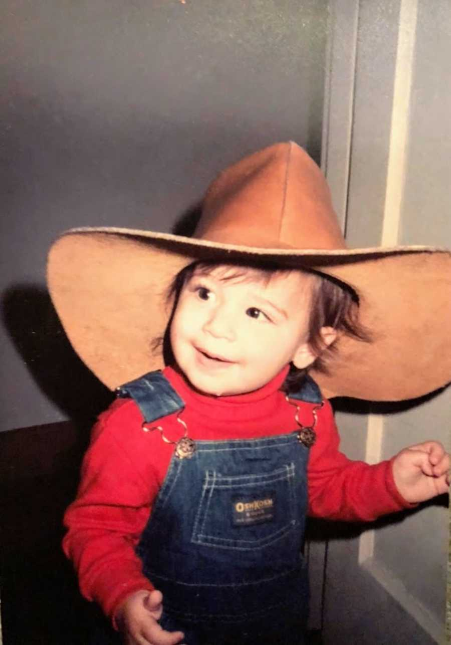 Toddler wearing cowboy hat and overalls
