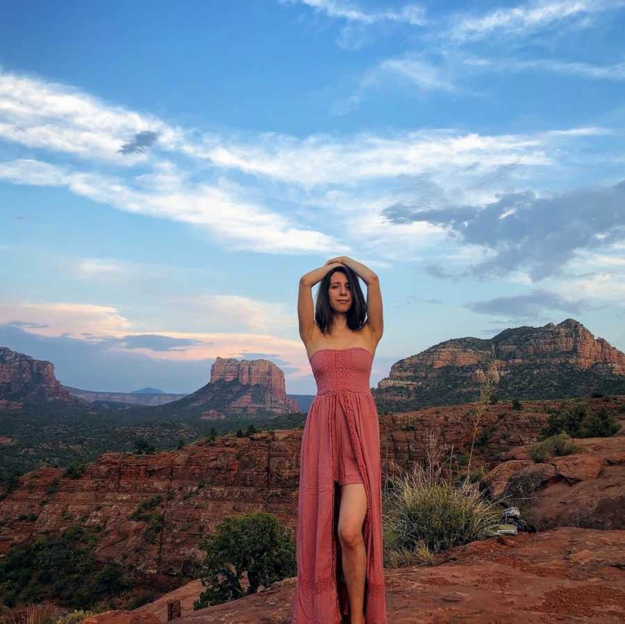 Woman wearing pink dress with arms on head in front of canyon