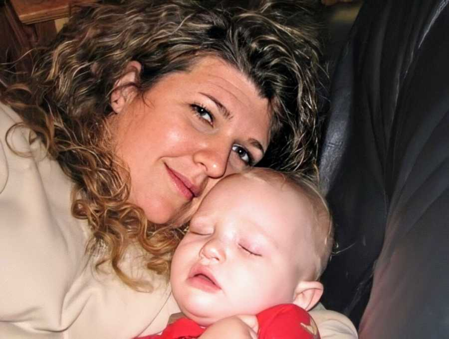 A woman cuddles with a sleeping toddler