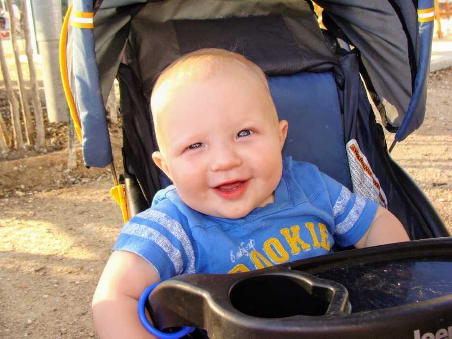 A boy wearing a blue T-shirt sits in a stroller
