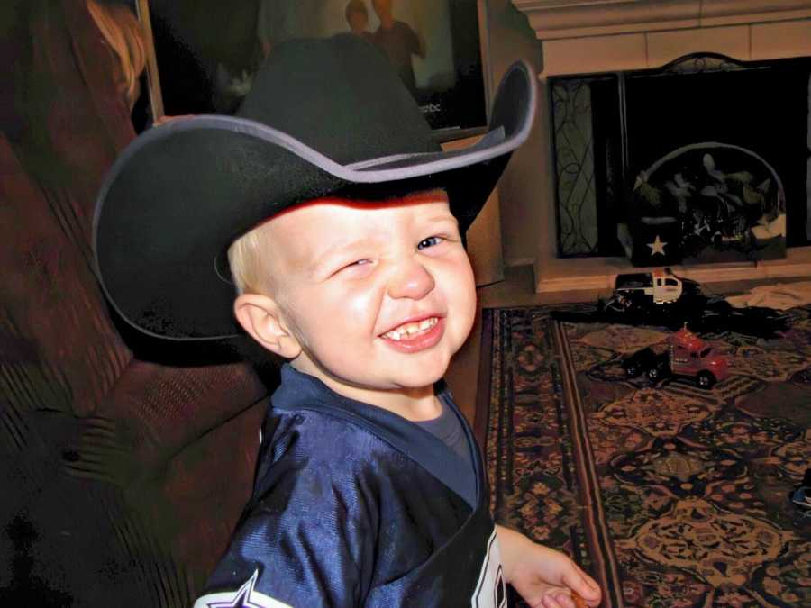 A boy wearing a jersey and a cowboy hat smiles and winks at the camera