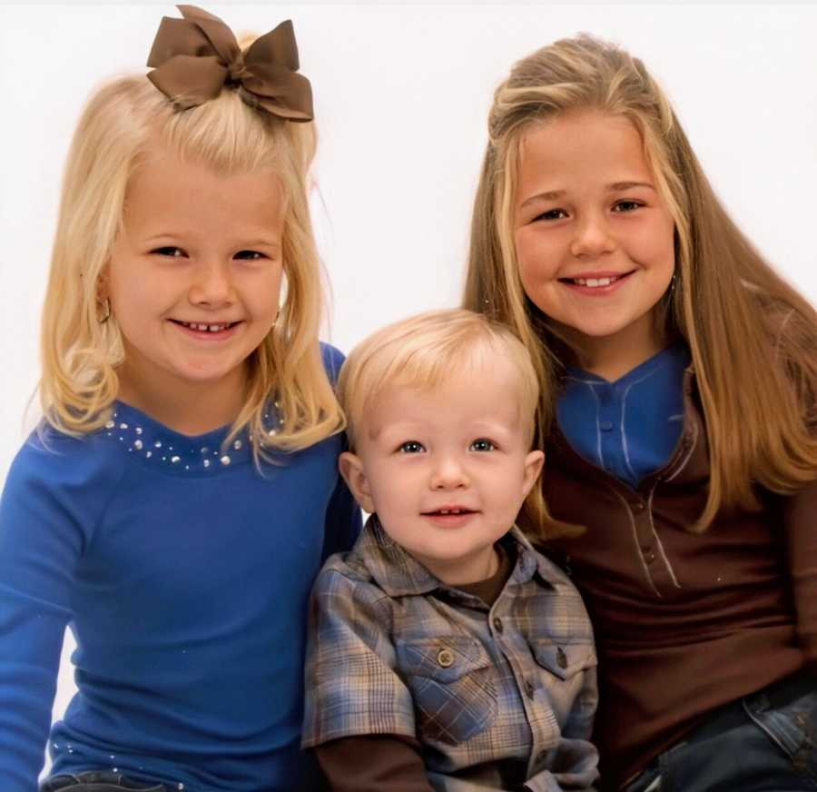 A young boy sits with his older sisters