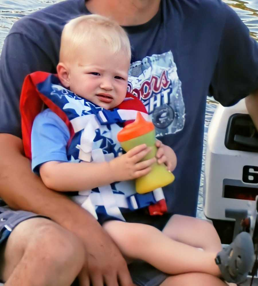 A boy wearing a life vest holds a sippy cup while on a man's lap