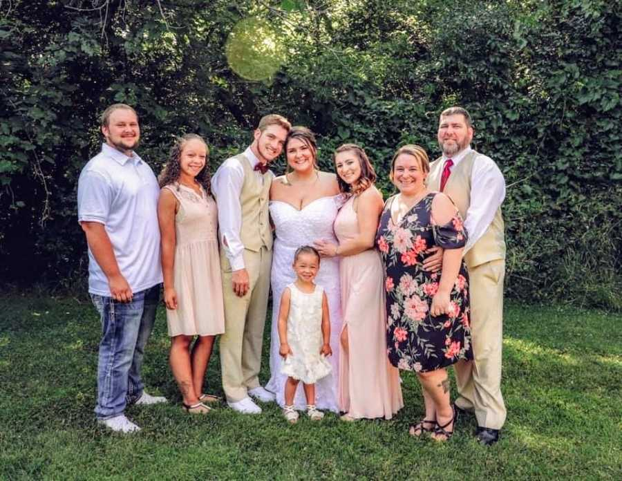 A bride and groom surrounded by their family