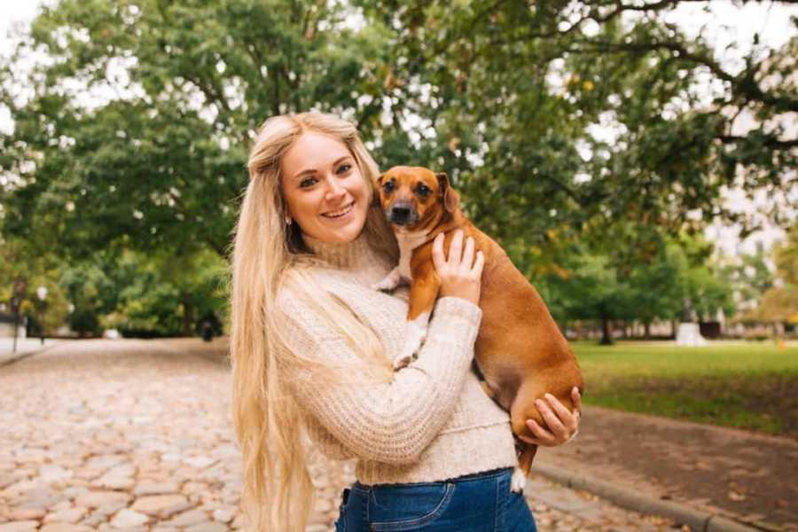 Blonde girl smiling standing outside holding brown weiner dog