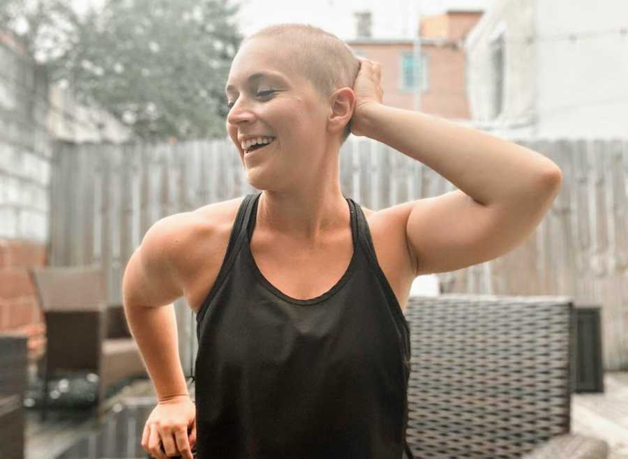 Woman with buzzcut smiling and sitting outside on patio