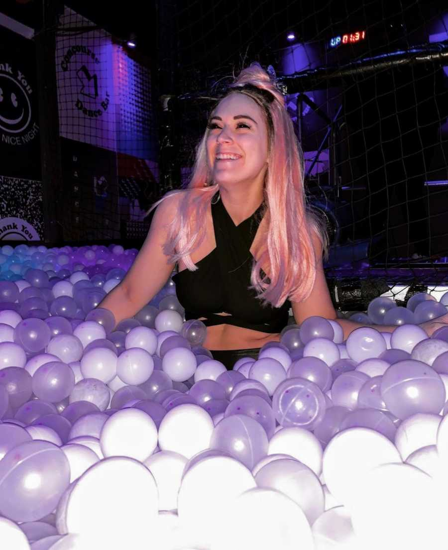 Woman standing in purple ball pit wearing pink wig