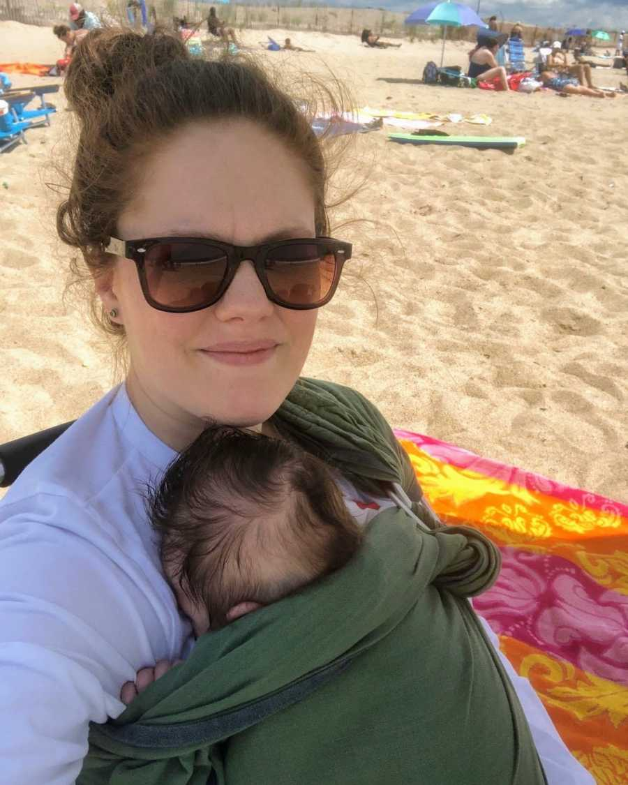 Mother holding swaddled newborn baby on sunny beach day