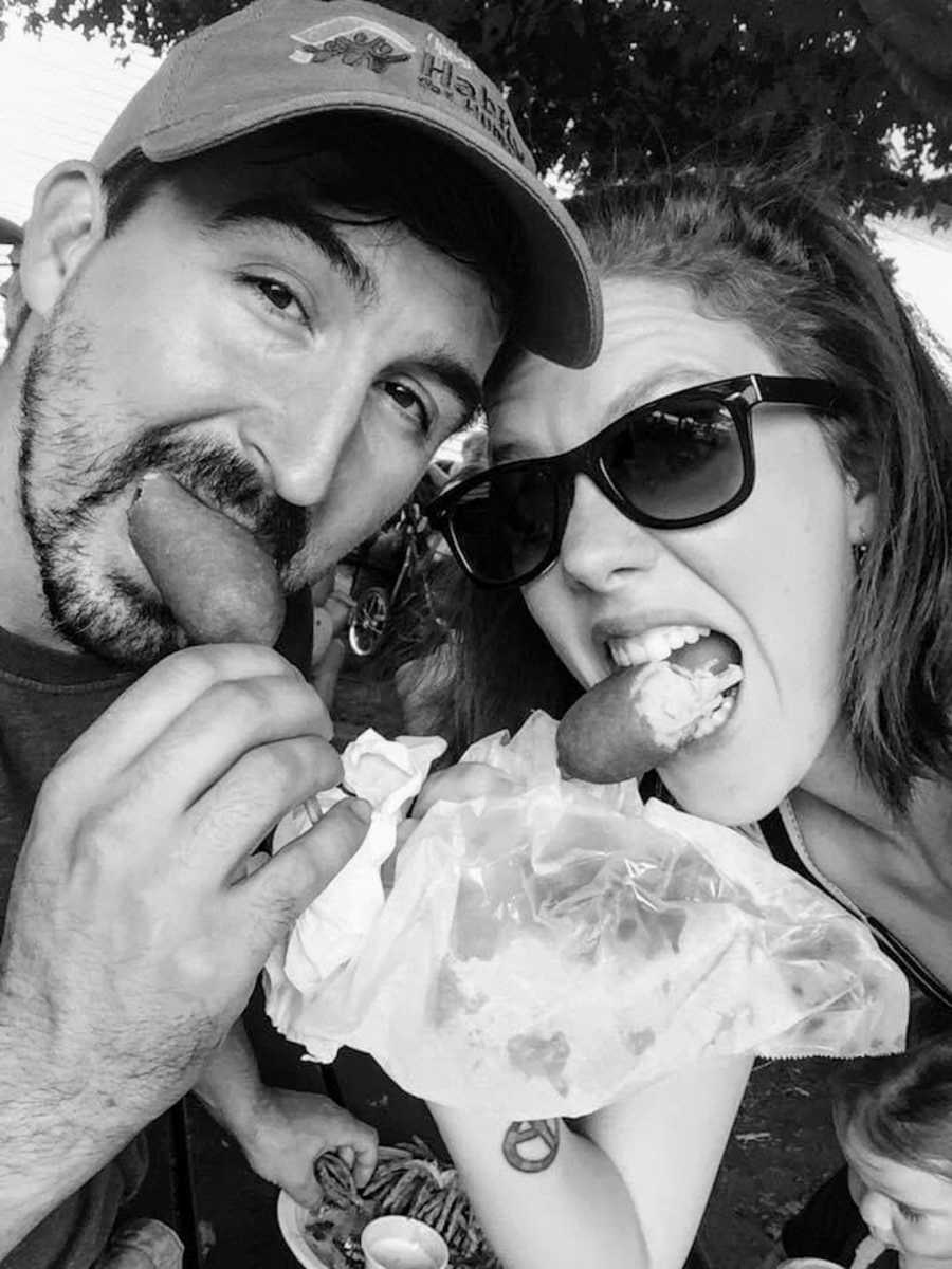 Black and white photo of husband and wife eating corndogs