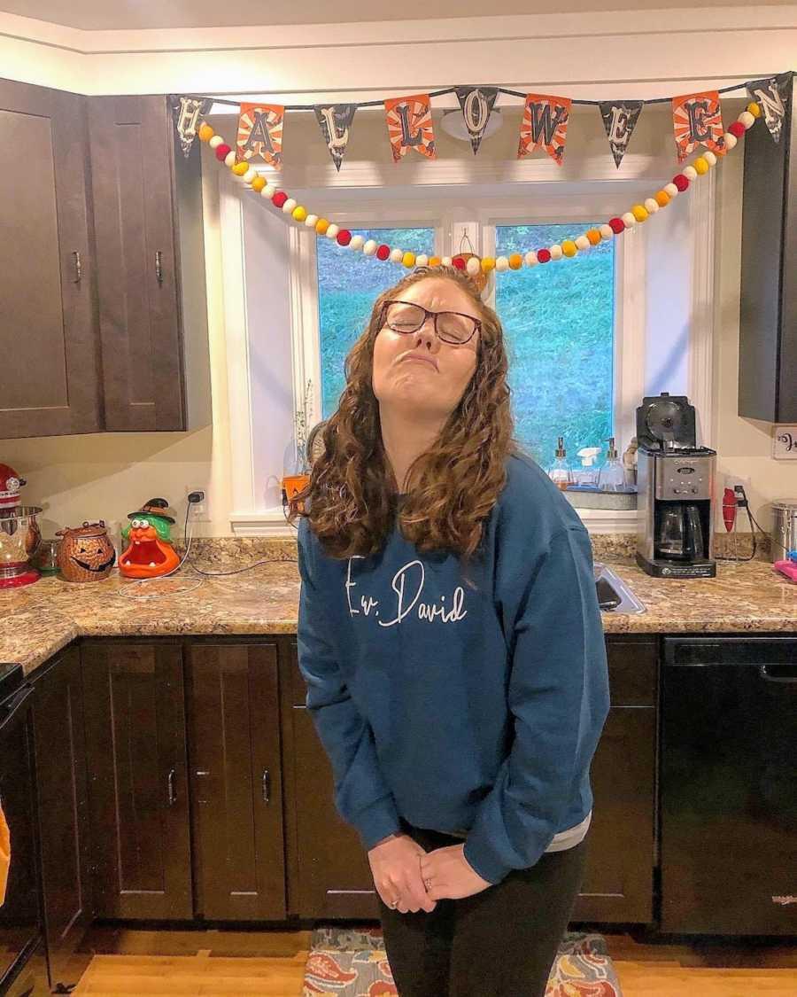 Woman wearing Schitt's Creek sweatshirt standing in kitchen with Halloween decorations