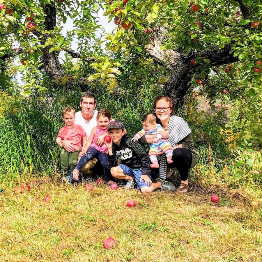 Family of 6 squatting outside by trees and grass and smiling