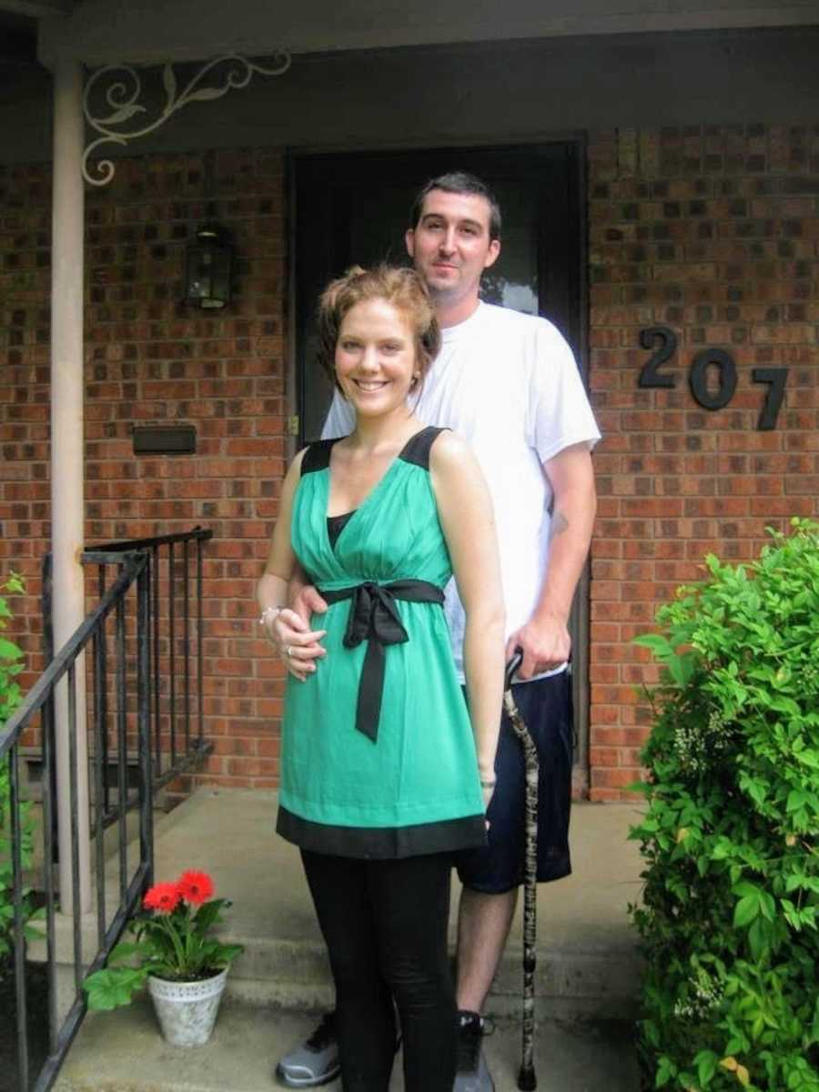 Husband and wife standing on front steps of brick house